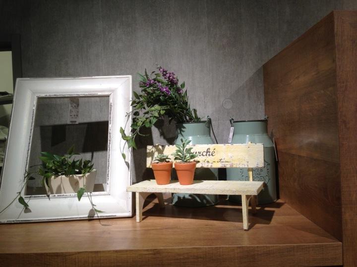 ミニチュアのベンチ、ピクチャーフレームの付いた植木鉢がディスプレイされている。