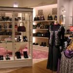 プリムローズ店舗内、白い木枠組みの棚に靴が置かれ、周囲に服が掛けられている。