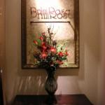 コンソールの上に花を活けた花瓶が置かれ、その上にPrimroseロゴの額が飾られている。