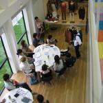 吹き抜け上部から見下ろしているのは、テーブルの周りに座る店長たち。